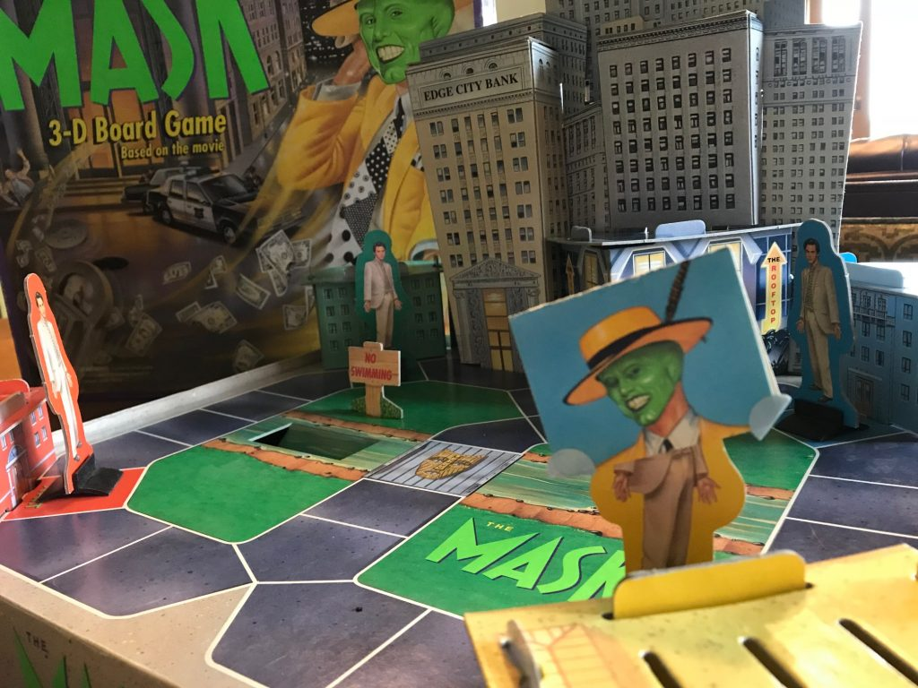 The board showing 3-d buildings and Stanley pawns, one wearing a mask