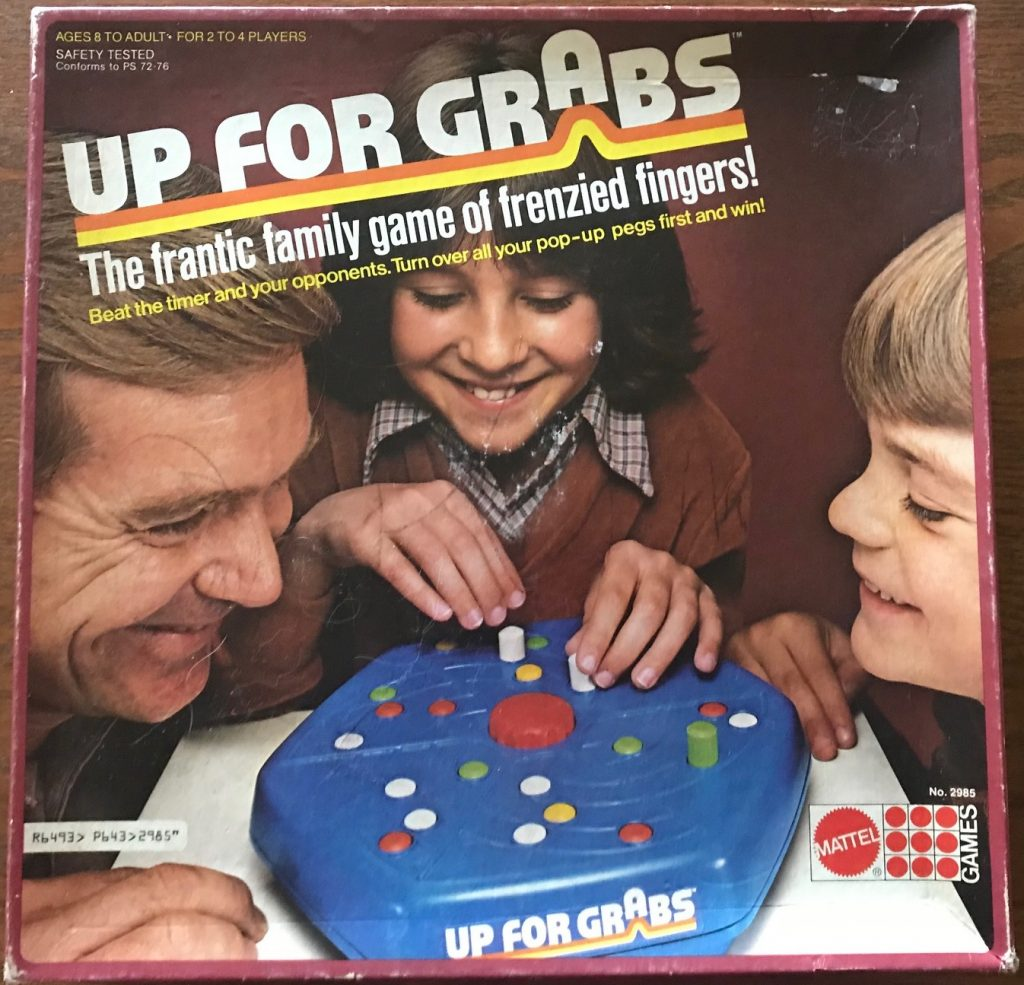 Cover shows family of 3 leaning over the game piece