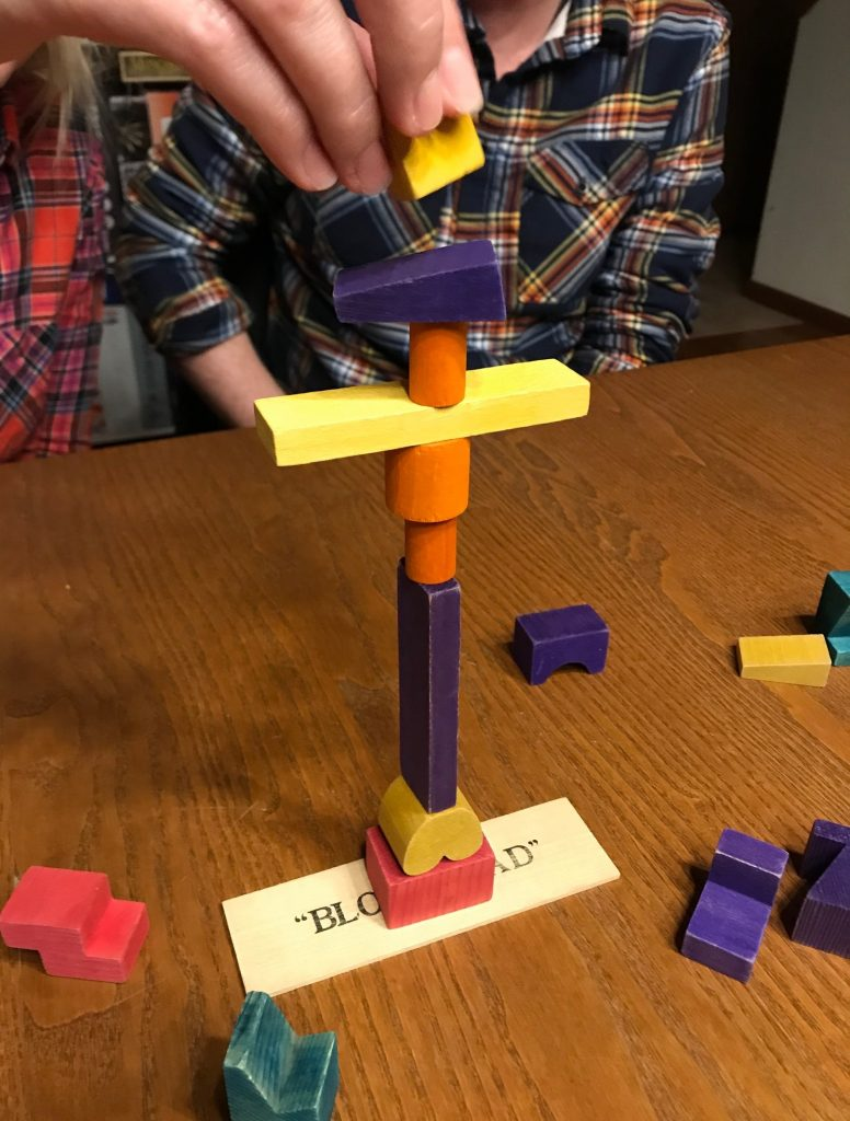 An action shot showing a hand placing a block on a structure that is already 9 blocks tall