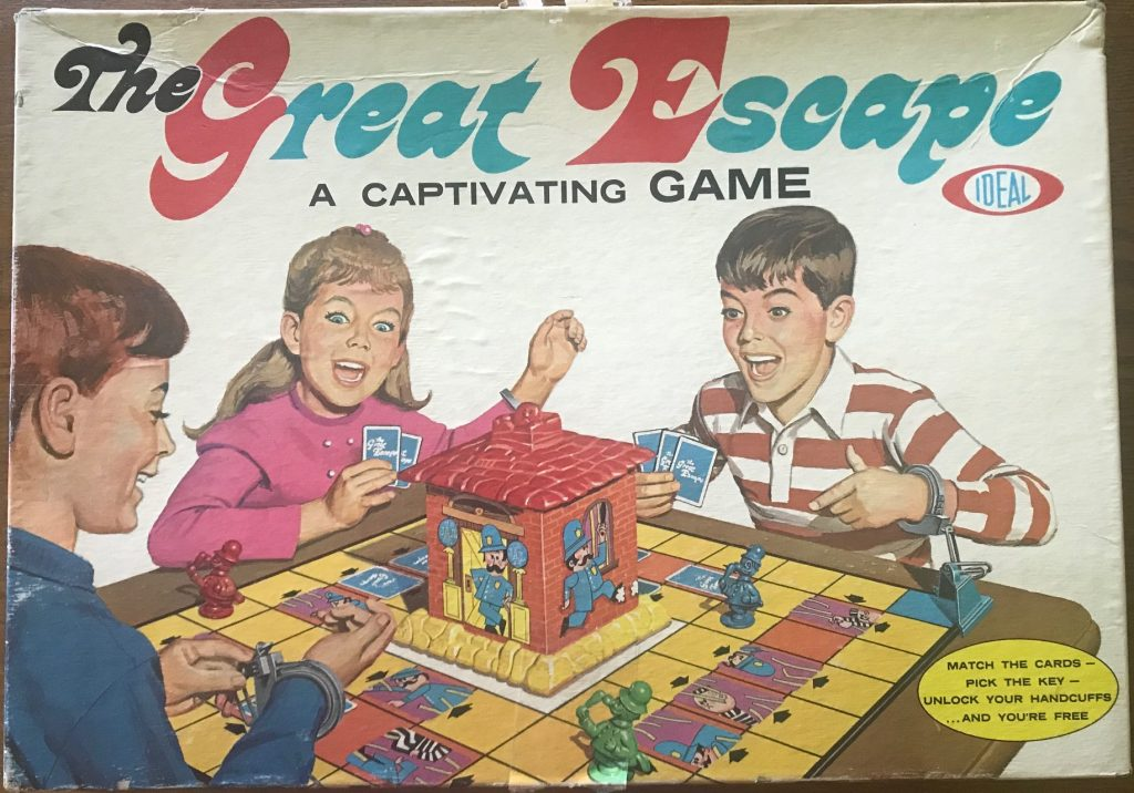Three children looking excited while handcuffed to a game board