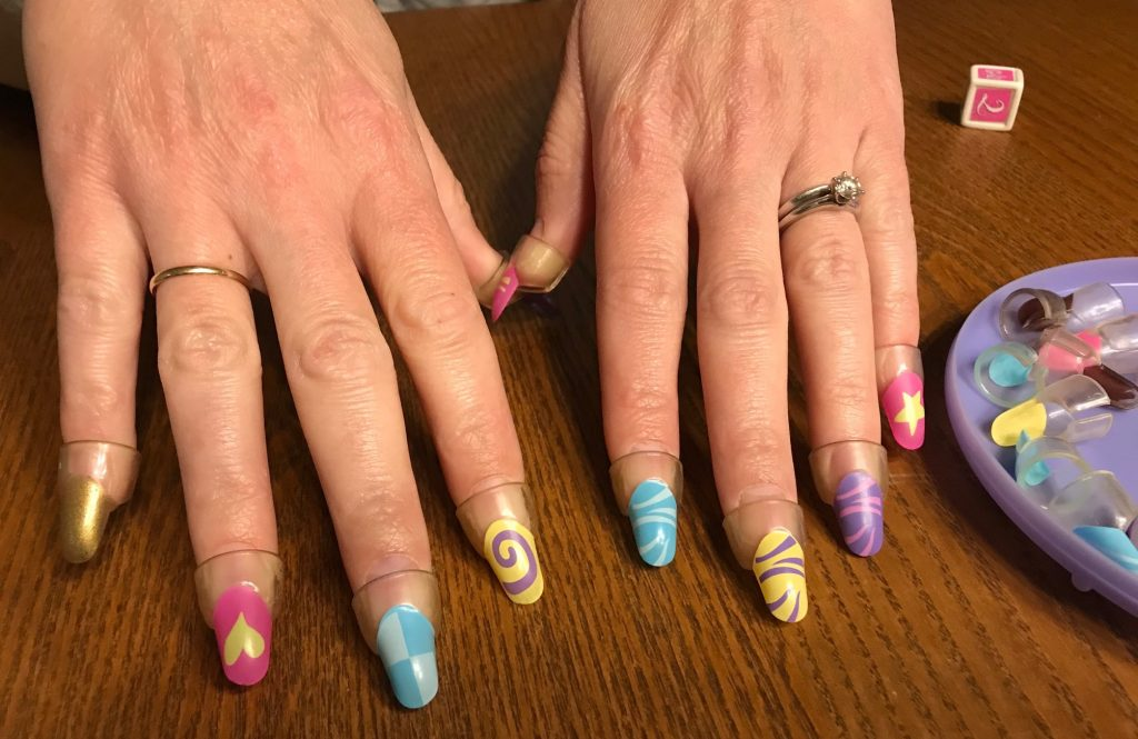 Two hands showing one gold nail and 9 funky fingernails