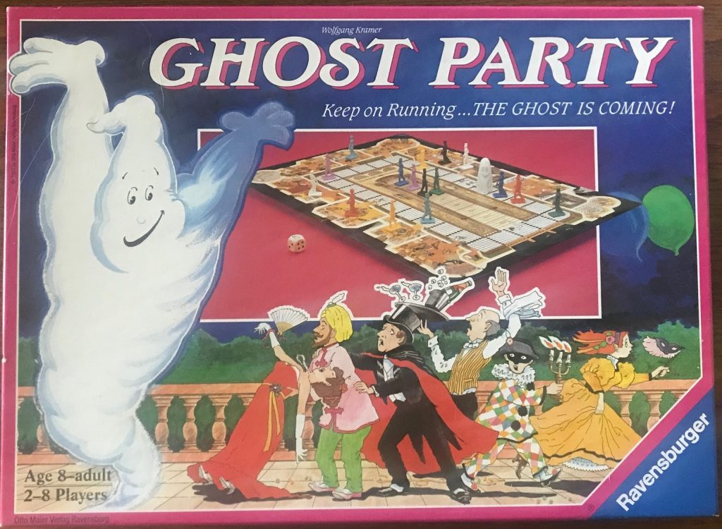 This cover has a ghost with its arms up on the left side, a large image of the board in the upper middle and the cartoon characters in the lower middle