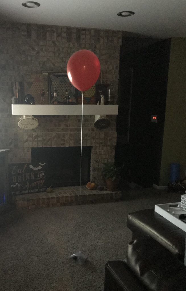 A red balloon in a dark living room