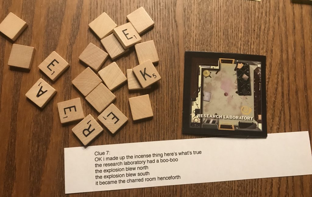 This clue includes Scrabble tiles and is described below