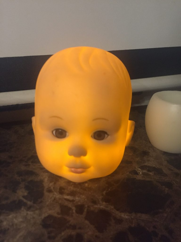 A baby doll head lit from inside by an LED candle