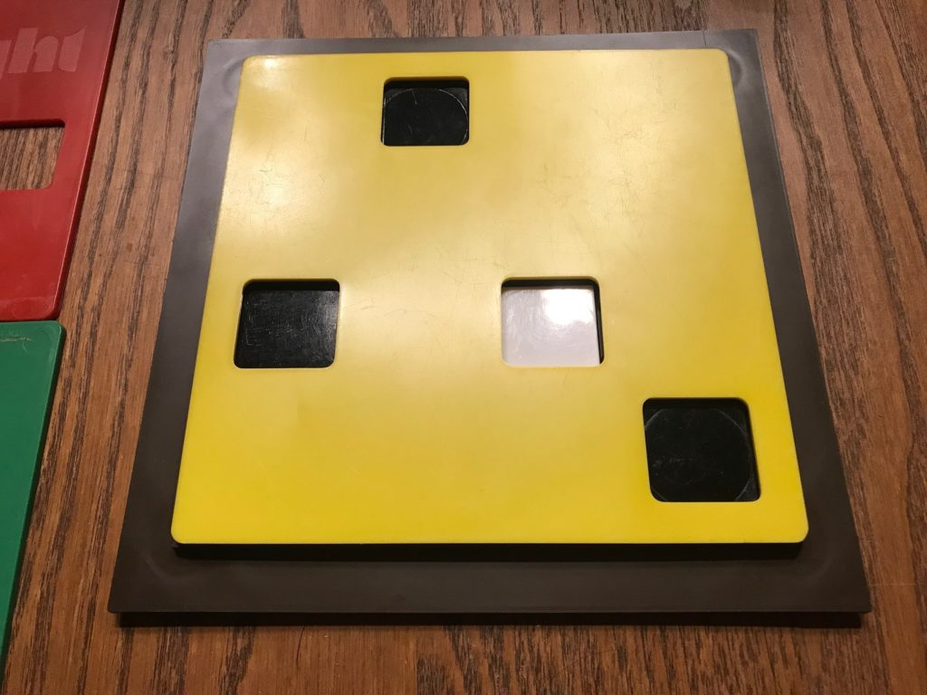 The board with a yellow KEY PLATE on it showing three black TABLETS and one white TABLET